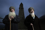 Two elders of Vedeno highland region in Chechnya pose by the ancestry tower, ruined by the Soviets and rebuilt anew upon their return from exile.